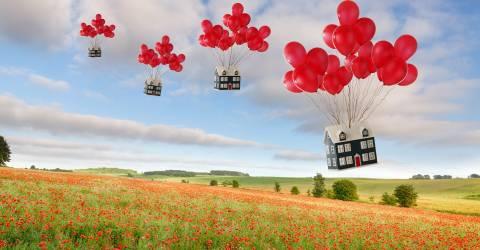 Huizen die vast zitten aan ballonnen en over een bloemenveld vliegen